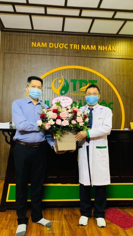 Ông Nguyễn Quang Hưng tặng hoa cho bác sĩ Lê Hữu Tuấn
